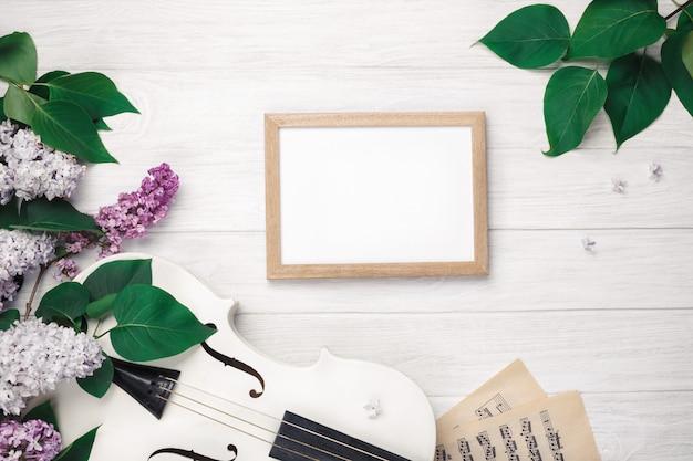 Un bouquet de lilas avec violon, tableau noir et partition sur une table en bois blanche. top wiev avec un espace pour votre texte