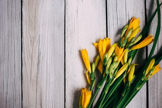 Bouquet de lis jaunes sur un fond en bois, bouquet de mariée