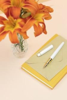 Bouquet de lis orange dans un vase avec cahier jaune et enveloppe
