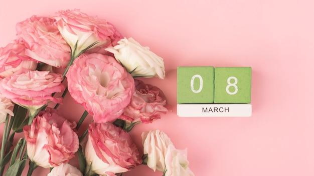 Bouquet de lisianthus rose sur une table rose, calendrier avec la date du 8 mars