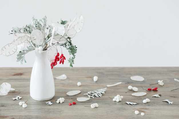 Bouquet de lunaire et de fruits rouges dans un vase blanc sur l'onglet en bois