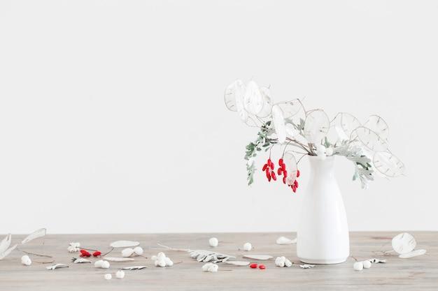 Bouquet de lunaire et de fruits rouges dans un vase blanc sur table en bois