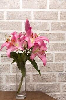 Bouquet de lys roses dans un vase en verre sur un mur de briques gris clair
