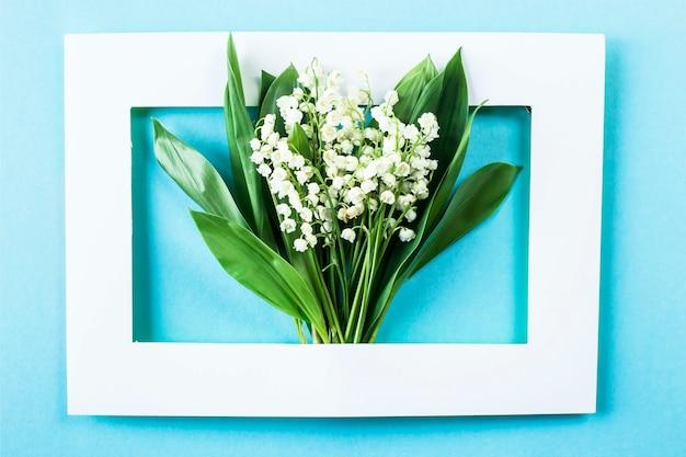 Un bouquet de lys de la vallée dans un cadre blanc sur fond bleu