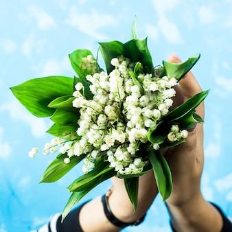 Un bouquet de lys de la vallée dans des mains féminines sur fond bleu