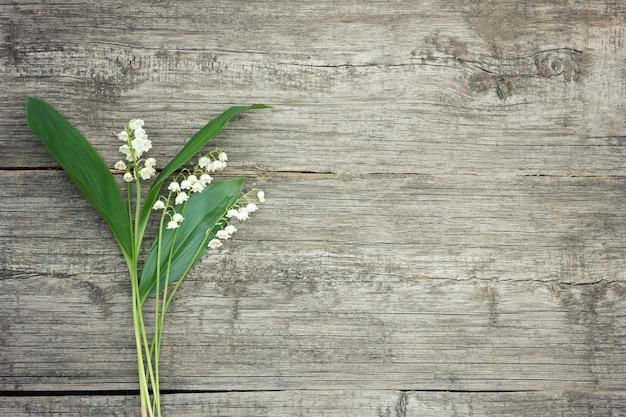 Bouquet de lys de la vallée sur un fond en bois.