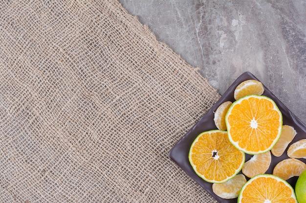 Bouquet de mandarine et segments sur plaque noire.