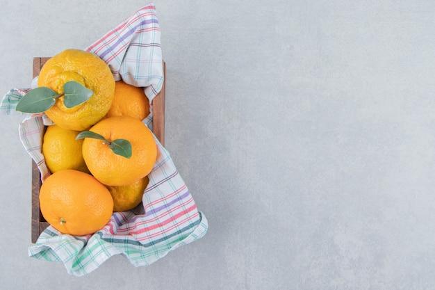 Bouquet de mandarines fraîches dans une boîte en bois.