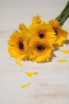 Bouquet de marguerite jaune sur table en bois.