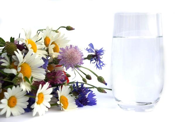 Un bouquet de marguerites à côté d'un verre d'eau