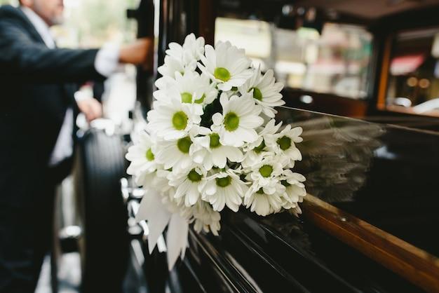 Bouquet de marguerites décorant une voiture de mariage antique.