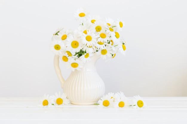 Bouquet de marguerites sur mur blanc