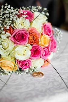 Bouquet de mariage coloré fait de roses se trouve avant les anneaux sur une table