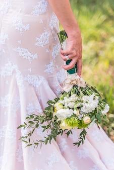 Bouquet de mariage dans les mains de la mariée sur fond de robe