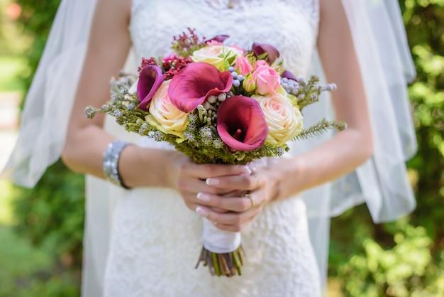 Bouquet de mariage de diverses belles fleurs dans les mains de la mariée en robe blanche et voile agrandi