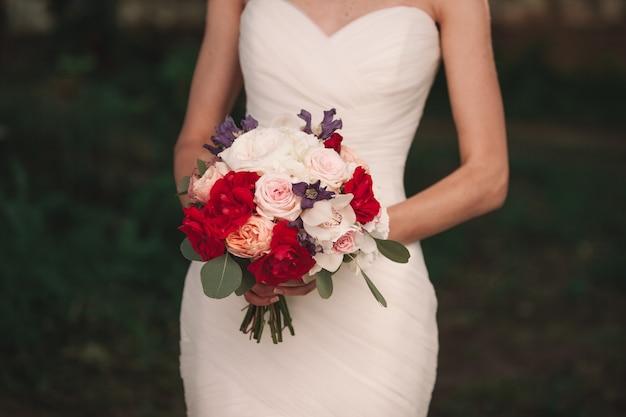 Bouquet de mariage entre les mains de la mariée.