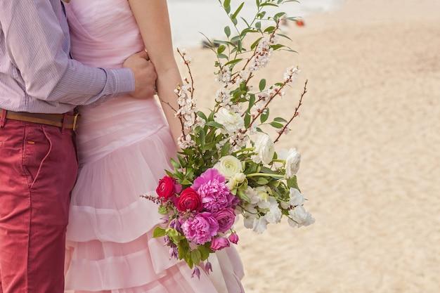 Un bouquet de mariage est entre les mains de la fiancée