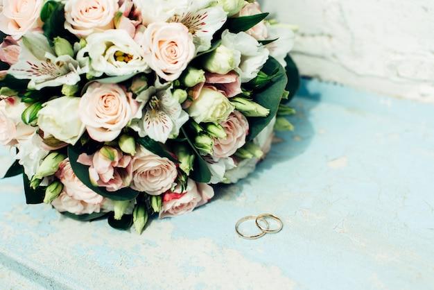 Bouquet de mariage de fleurs avec des anneaux sur bleu clair
