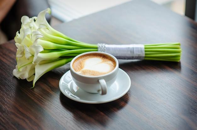 Bouquet de mariage de lis calla sur une table avec une tasse de café.