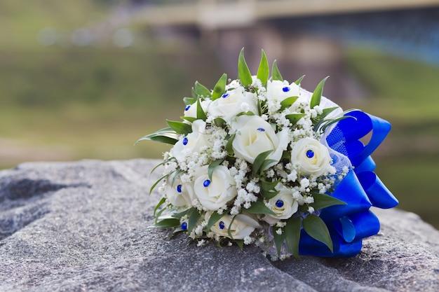 Bouquet de mariage de roses blanches allongé sur une pierre