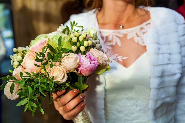 Bouquet de mariage de roses avec un ruban rose dans les mains de la mariée, la mariée tient un bouquet de roses de mariage
