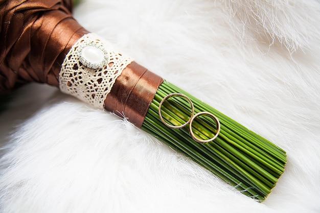 Bouquet de mariée et anneaux sur fond blanc