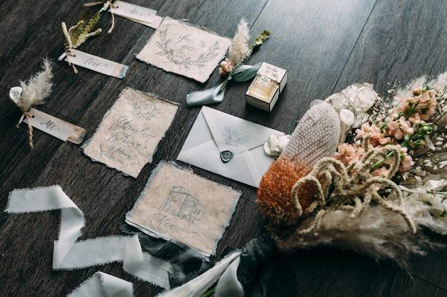 Bouquet de mariée arts graphiques et rustiques de belles cartes de calligraphie avec des bobines de fleurs et de mousseline sur table en bois. belle invitation de mariage. vue de dessus.