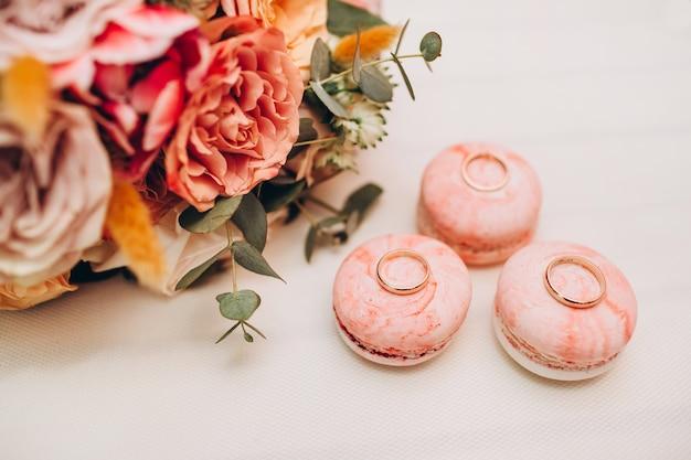 Bouquet de mariée aux couleurs de l'automne, bagues de mariage et macarons sur un tableau blanc.