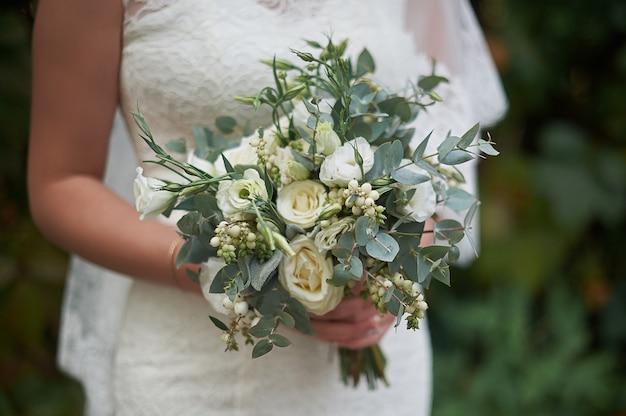 Bouquet de mariée blanche dans les mains de la mariée.