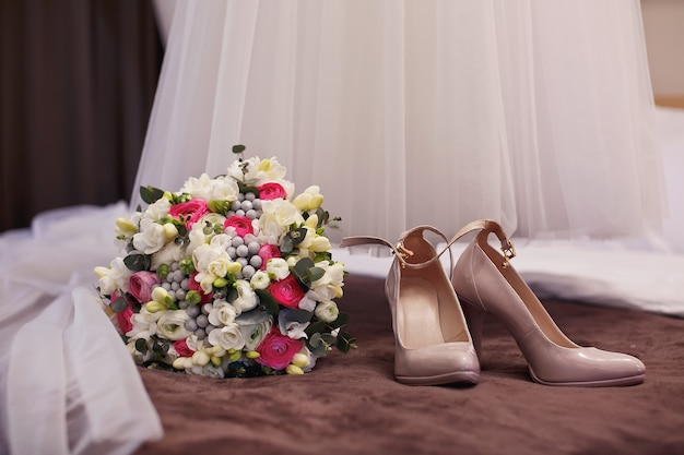 Bouquet de mariée avec des chaussures dans la chambre de la mariée