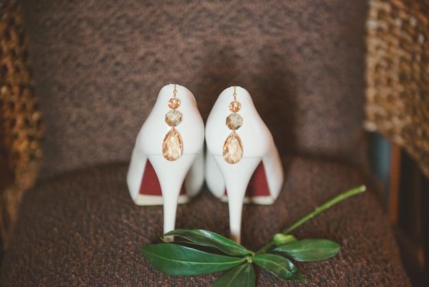 Bouquet de mariée, chaussures femme beige sur mur sombre avec des feuilles vertes