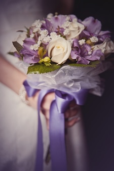 Bouquet de mariée dans les mains de la mariée avec du ruban violet