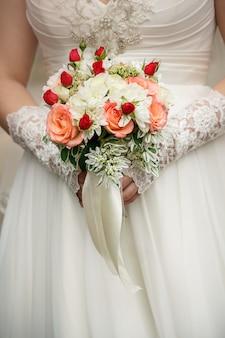 Bouquet de mariée dans les mains de la mariée avec un ruban blanc