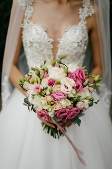 Bouquet de mariée dans les mains de la mariée