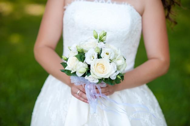 Bouquet de mariée dans les mains de la mariée.