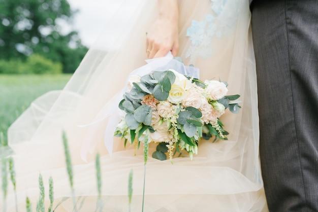 Bouquet de mariée délicat élégant dans les mains de la mariée sur le fond de la robe de mariée