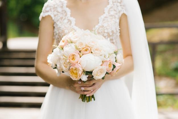 Bouquet de mariée délicat entre les mains d'un gros plan de mariée sophistiqué