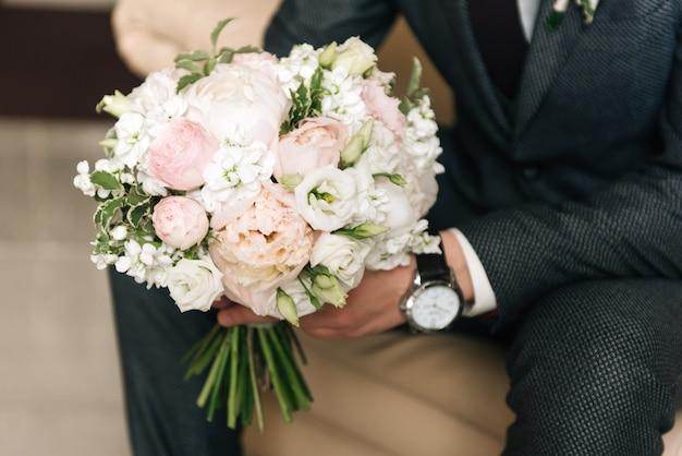 Bouquet de mariée entre les mains du marié, mise au point sélective