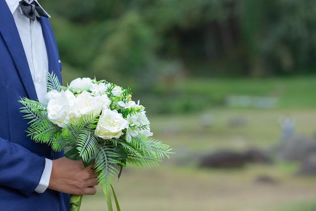 Bouquet de mariée entre les mains du marié.
