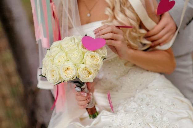 Bouquet de mariée entre les mains de la mariée de roses.