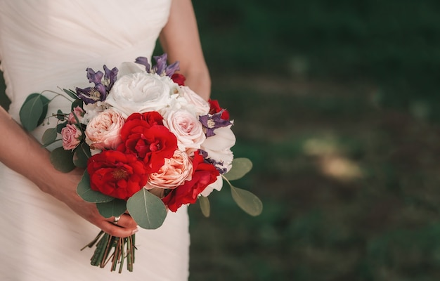 Bouquet de mariée entre les mains de la mariée, vacances et traditions