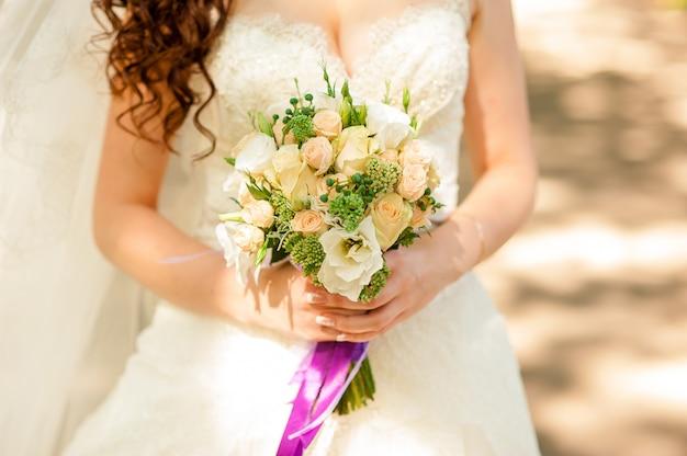 Bouquet de mariée entre les mains de la mariée