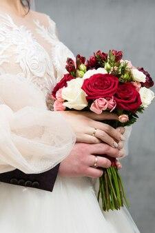 Bouquet de mariée entre les mains des mariés