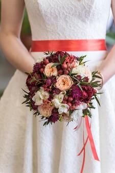 Bouquet de mariée entre les mains de