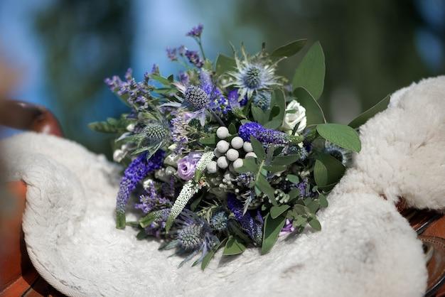 Bouquet de mariée avec des fleurs blanches, vertes et bleues sur la selle d'un cheval