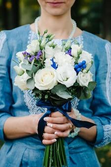 Bouquet de mariée fleurs dans les mains, sur le fond élégant femme mariée portant une robe brodée détient un bouquet.