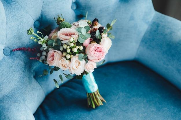 Bouquet de mariée de fleurs sur le fauteuil. fleurs de la mariée. de belles roses