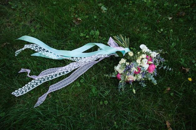 Bouquet de mariée de fleurs fraîches avec des rubans colorés et menthe sur l'herbe verte. fleurs de mariage pour la mariée.