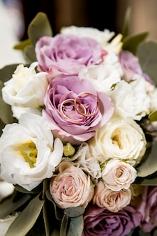 Bouquet de mariée avec des fleurs violettes et blanches et des anneaux