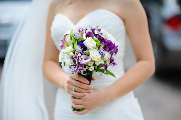 Bouquet de mariée de fleurs violettes et blanches dans les mains de la mariée